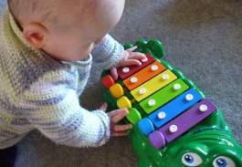 Baby with crocodile glockenspiel